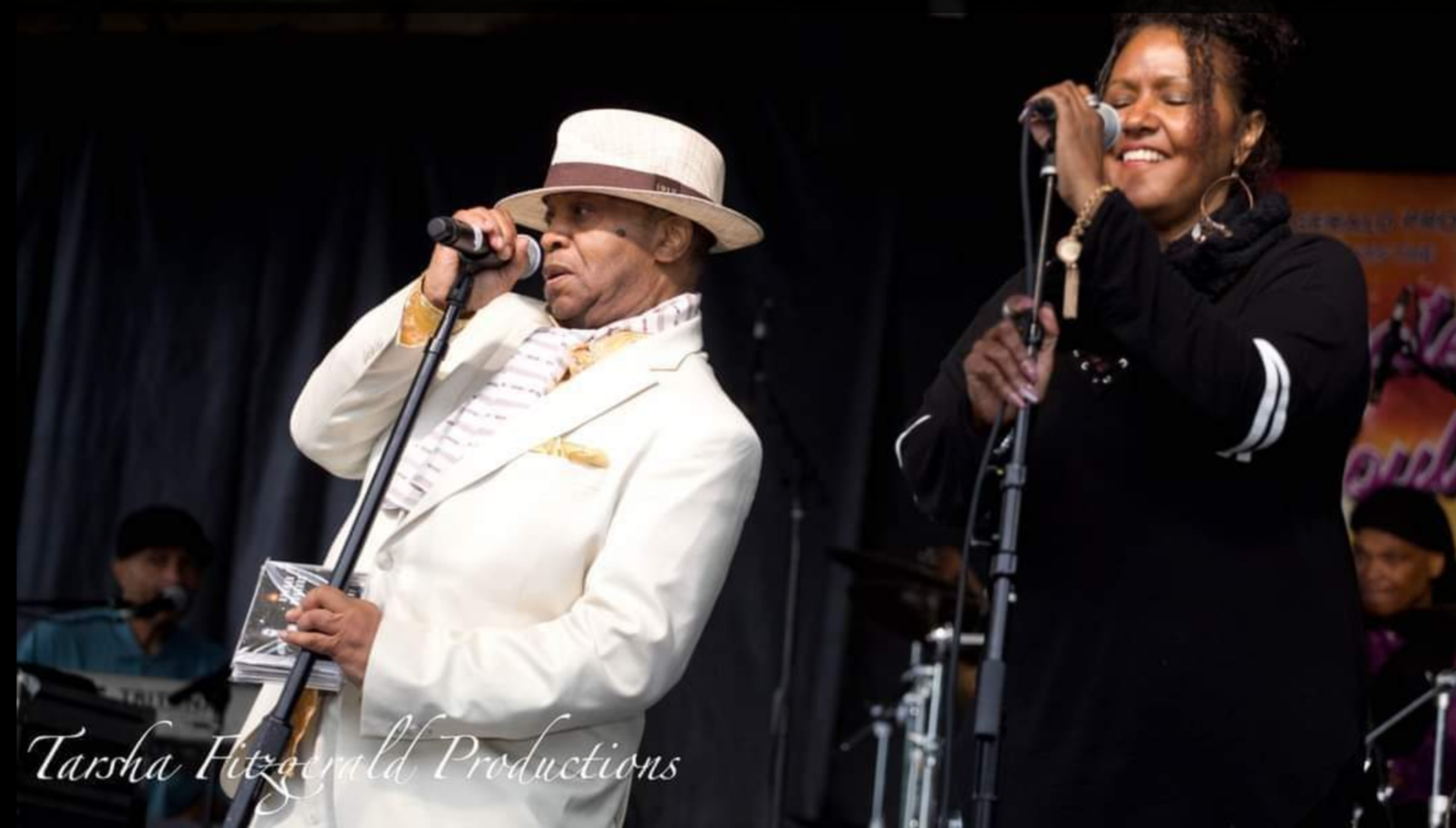 Norman Connors sings onstage with fellow vocalist